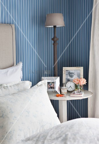 Framed photos, vintage alarm clock and bedside lamp on bedside table against blue and white striped wallpaper