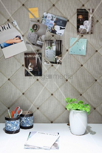 Postcards stuck on elegant fabric-covered pinboard above pen holders and vase of flowers on white desk