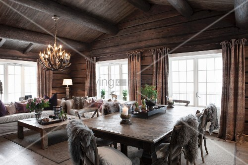 Grey fur blankets on chairs around solid wooden table and comfortable lounge area in open-plan interior of rustic wooden house