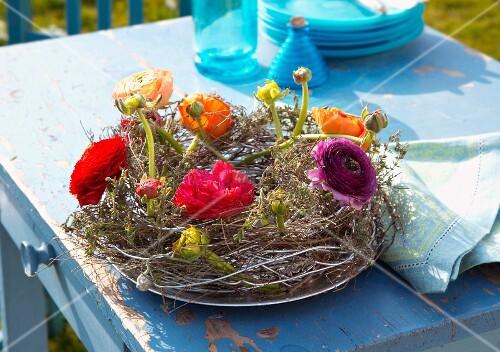 Kranz aus Geflecht und verschiedenfarbigen Ranunkeln auf Gartentisch
