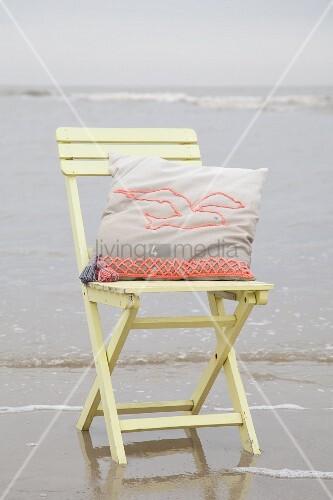 Kissen mit gehäkeltem Möwenmotiv auf Holzstuhl am Strand