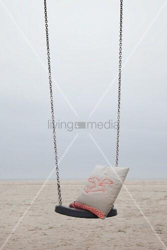 Kissen mit gehäkeltem Möwenmotiv auf Schaukel am Strand