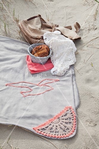 Hellgraue Picknickdecke mit gehäkelter Bordüre und Möwenmotiv im Sand
