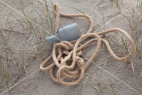 Seil und Plastikflasche auf Sandboden