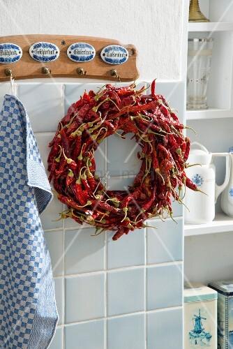Kranz aus getrockneten roten Chilischoten, an Wandhakenleiste in Küche aufgehängt