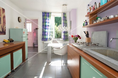 Retro kitchen; wooden cabinets with mint-green glass doors and dining area below window in background