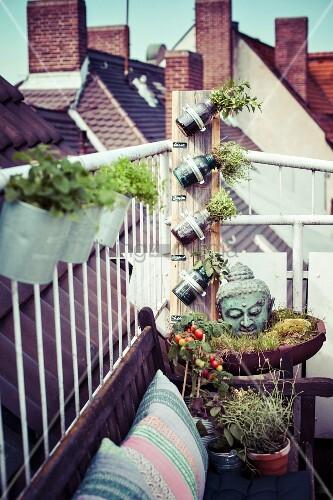 Buddhakopf und Pflanzenhalter aus Glasflaschen neben Sitzplatz auf städtischer Dachterrasse