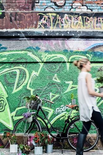 Mit Pflanzen dekoriertes Fahrrad vor mit Graffiti besprühter Wand