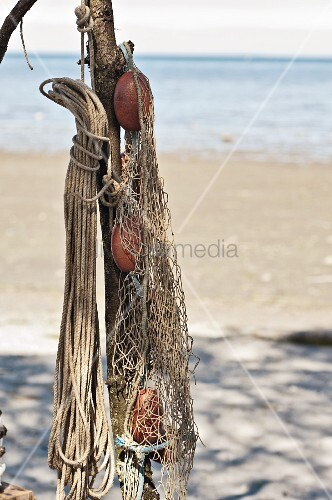Flotsam on sandy beach: ropes and fishing nets