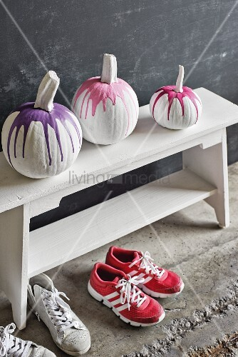 Painted pumpkins on white cloakroom bench above pairs of trainers