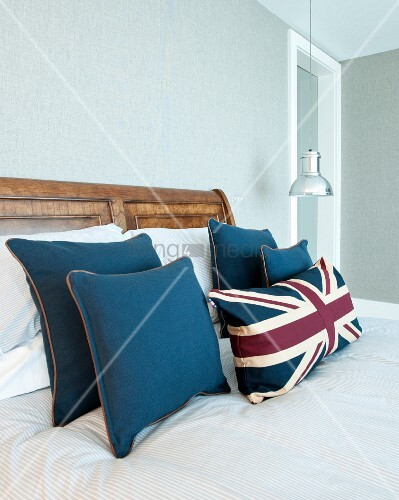 Blue and Union Flag scatter cushions on sold wooden bed; chrome pendant lamp in background