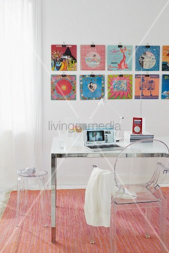 Record covers decorating the wall in front of a desk with a ghost chair