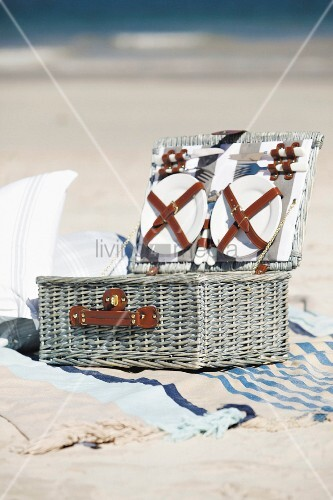 Open picnic basket on beach towel on sandy beach