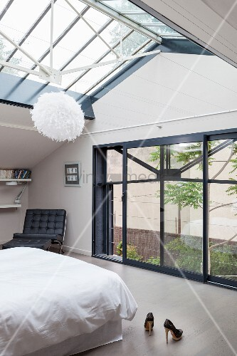 Light-flooded, elegant bedroom with glass roof and glass wall