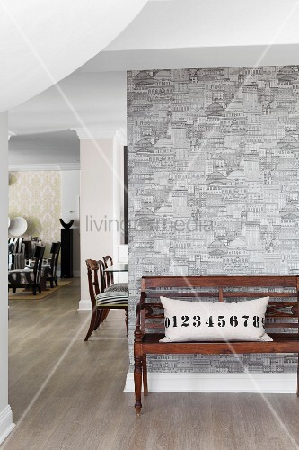 Numbers on scatter cushion on old wooden bench against patterned wallpaper in hall