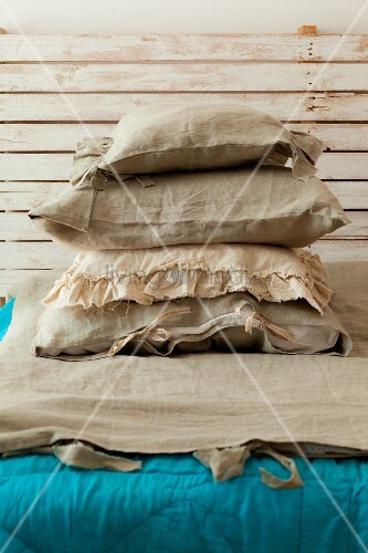 A stack of pillows with linen covers on a bed with a turquoise quilt and a rustic wooden headboard