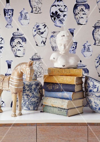 Bust of woman on stacked books, blue and white painted ceramic vase and bowls in front of wallpaper with pattern of vases