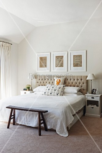 Bright bedroom with button-tufted headboard, white-framed drawings and rustic vintage bedroom bench