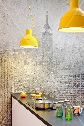 Pale grey New York skyline as background for kitchen counter below yellow pendant lamps