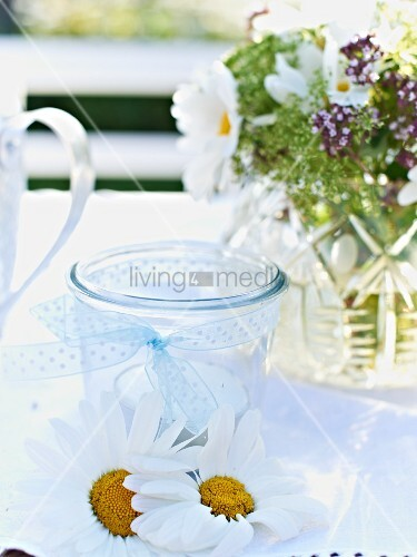 Tealight, ox-eye daisy flowers and posy of flowers decorating garden table