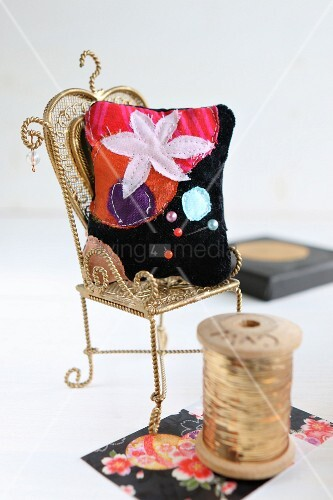 Hand-sewn, velvet pincushion with floral motif on miniature chair next to reel of gold thread