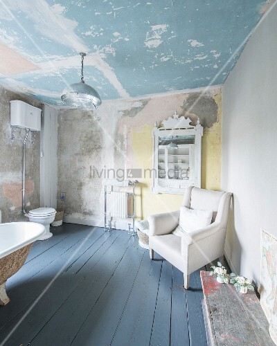 Armchair next to antique shelving, toilet and free-standing bathtub in large bathroom with patinated walls and ceiling