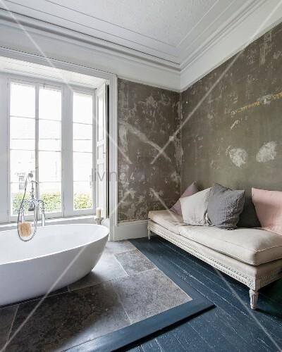 Ovale, freistehende Designerwanne auf Natursteinfliesen vor Fenster und antike Tagesliege vor patinierter Wand