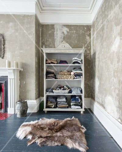 Clothes on open-fronted shelves in niche with patinated walls