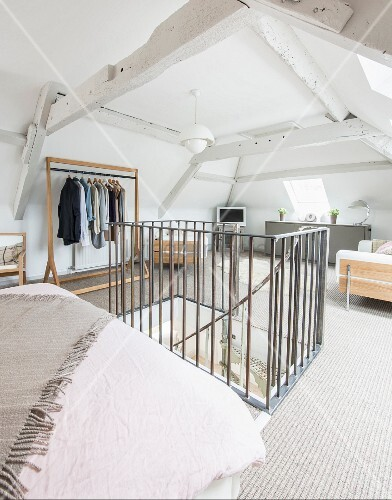Bedroom in converted attic with head of stairs in foreground