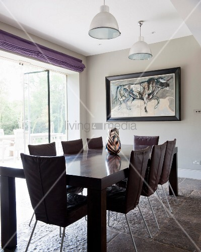 Dark wooden table and chairs on rustic stone floor next to terrace doors