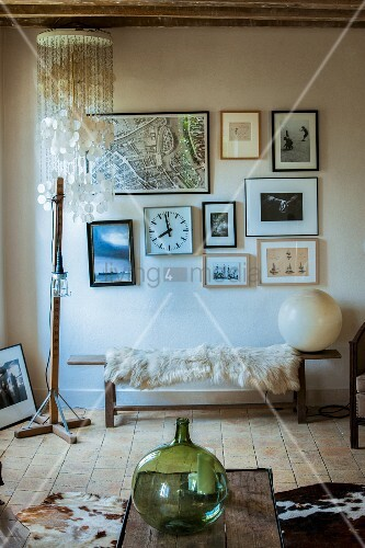 Green demijohn on coffee table, fur blanket on narrow wooden bench against wall below framed pictures