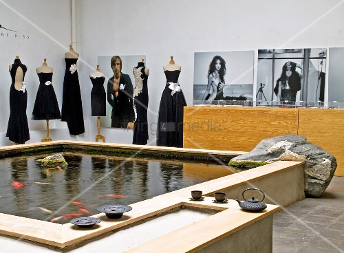 Large fish pond and elegant black clothing on tailors' dummies in couture studio
