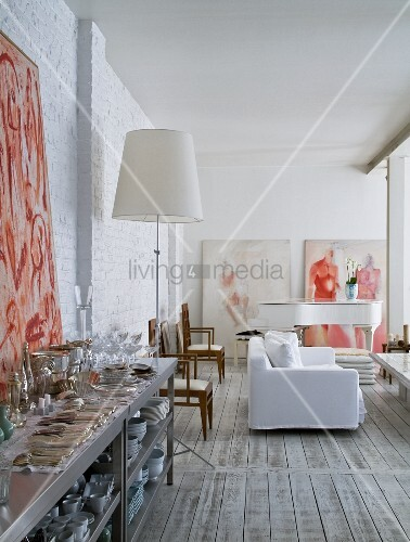 Cutlery and crockery on stainless steel shelving and white loose-covered sofa and grand piano in background of open-plan interior with whitewashed brick walls