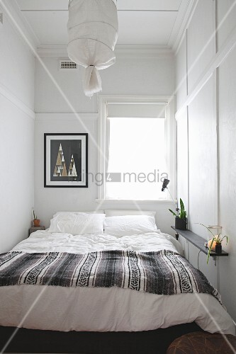 Double bed below window in narrow bedroom with simple, white-painted panelling on walls and ceiling