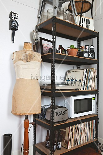Records, toaster and microwave on black metal shelves next to tailors' dummy and cat-shaped clock