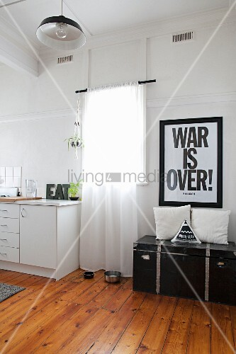 Poster with motto above vintage trunk next to window and simple kitchen counter in period apartment