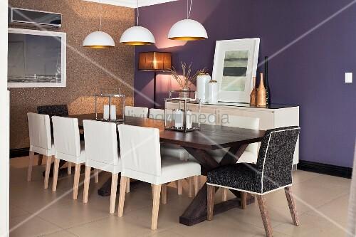 weisse lederst hle an langem esstisch aus dunklem holz dar ber pendelleuchten mit weiss. Black Bedroom Furniture Sets. Home Design Ideas