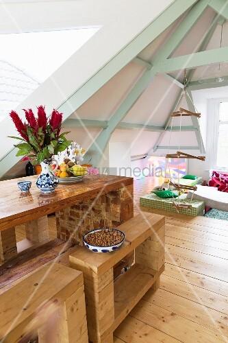Holztisch und Holzbänke vor Kinderbereich mit Klettergerüst in offener Dachkonstruktion