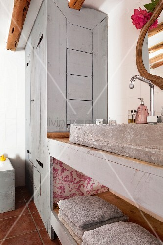 Rustic washstand with concrete sink and shelf in front of fitted wooden cupboard painted pale grey