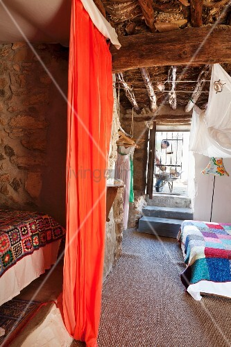Orange curtain screening sleeping area; bed with patchwork quilt in background