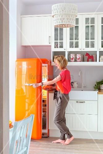 Woman in white, country-house kitchen with orange retro fridge
