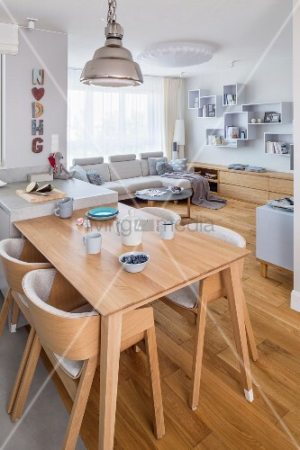 Open-plan interior with simple wooden furniture and pale sofa set in small apartment