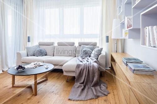 helle couch mit coffeetable vor fenster neben eingebautem sideboard aus hellem holz bild. Black Bedroom Furniture Sets. Home Design Ideas