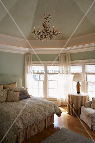 Edles Schlafzimmer mit Kronleuchter und pastellgrüner Wand- und ...