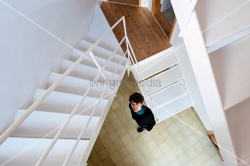 View down white steel staircase to woman standing in stairwell