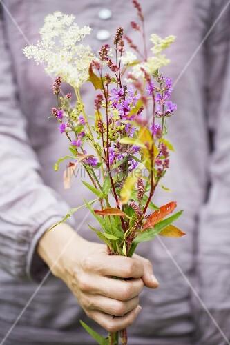 Bunch of various wildflowers held in hand