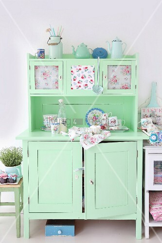 Hellgrünes Vintage-Küchenbuffet romantisch mit pastellfarbenem Blechgeschirr, Rosenmuster-Porzellan und Stoffen dekoriert