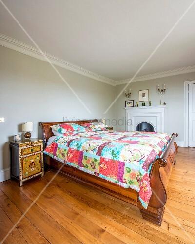 Elegantes, antikes Schlittenbett mit bunter Patchworkdecke und asiatisches Nachtkästchen in schlichtem Schlafzimmer