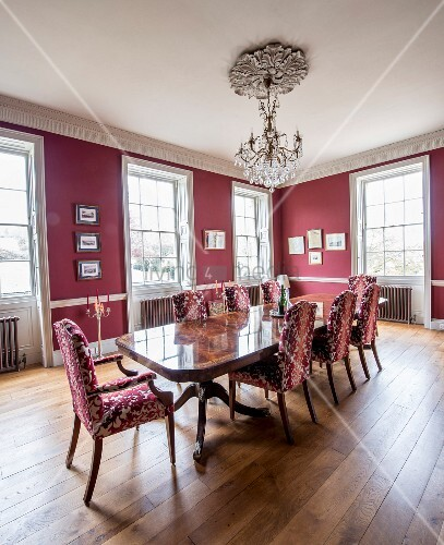 Chairs with patterned upholstery around polished wooden table below chandelier in grand dining room with red walls