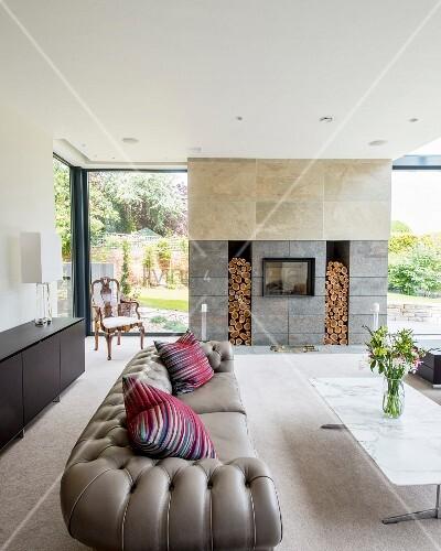 Graues Chesterfield-Sofa und Marmor-Couchtisch vor modernem Kamin ...